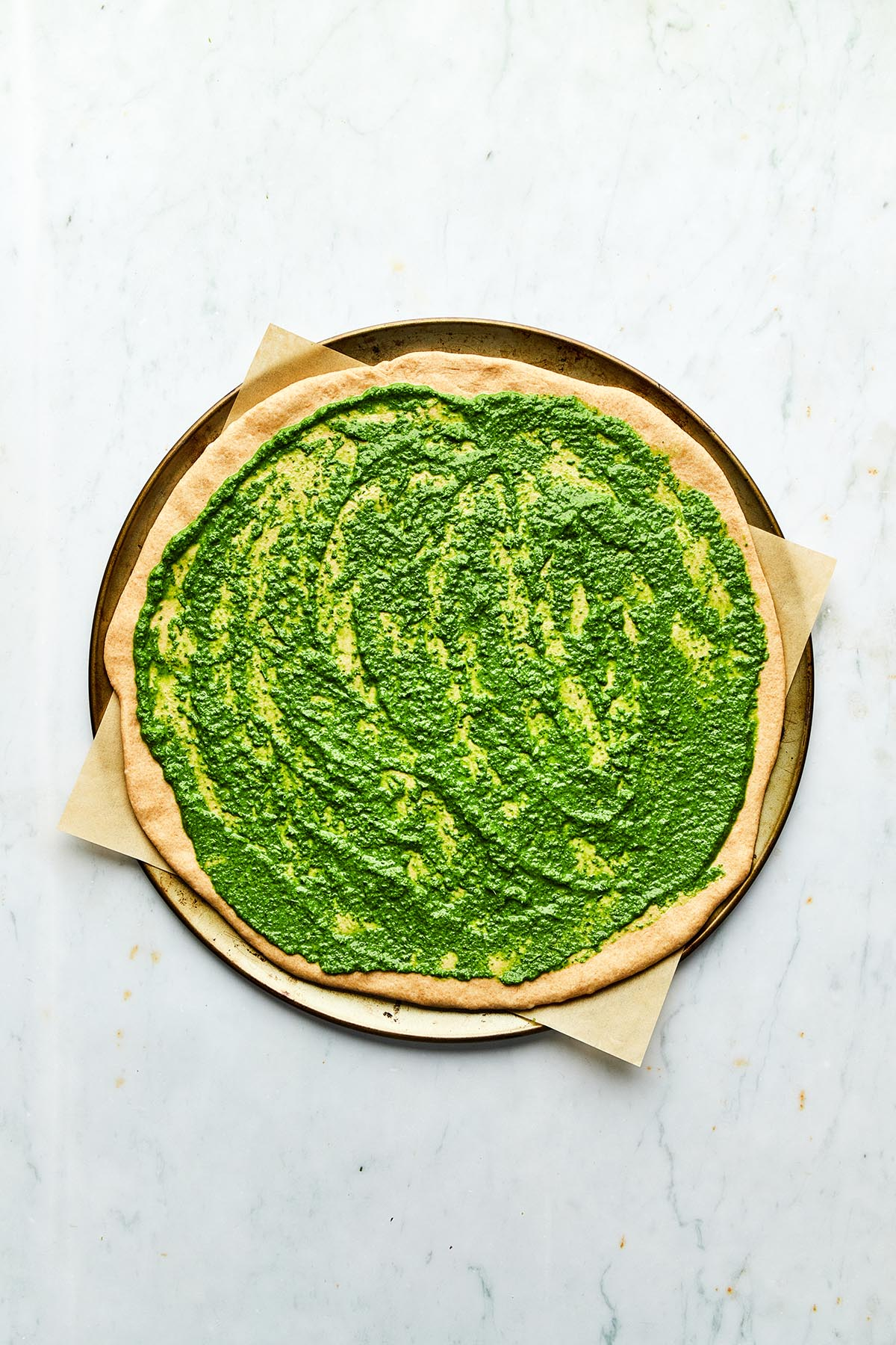 An unbaked pizza spread with green pesto as the base.