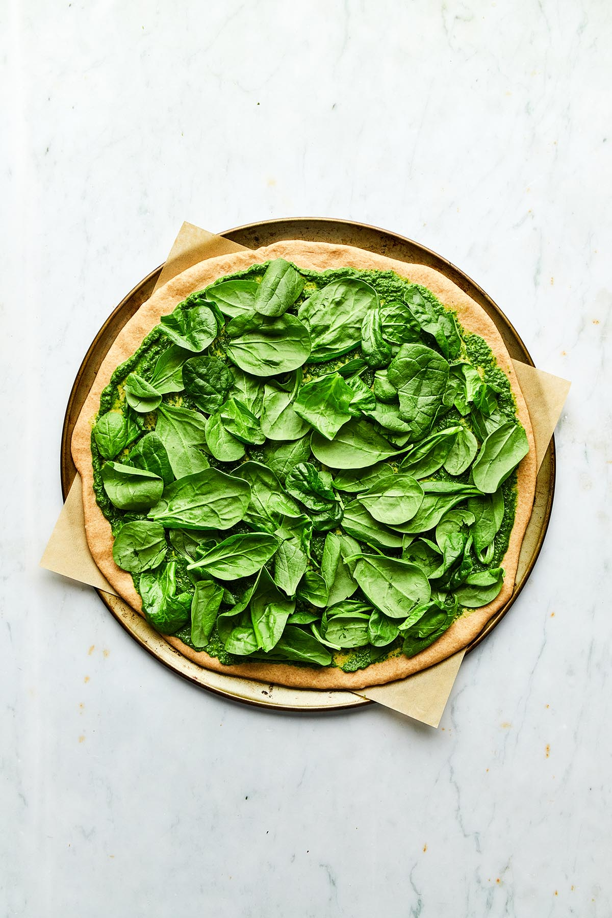 An unbaked pizza topped with spinach.