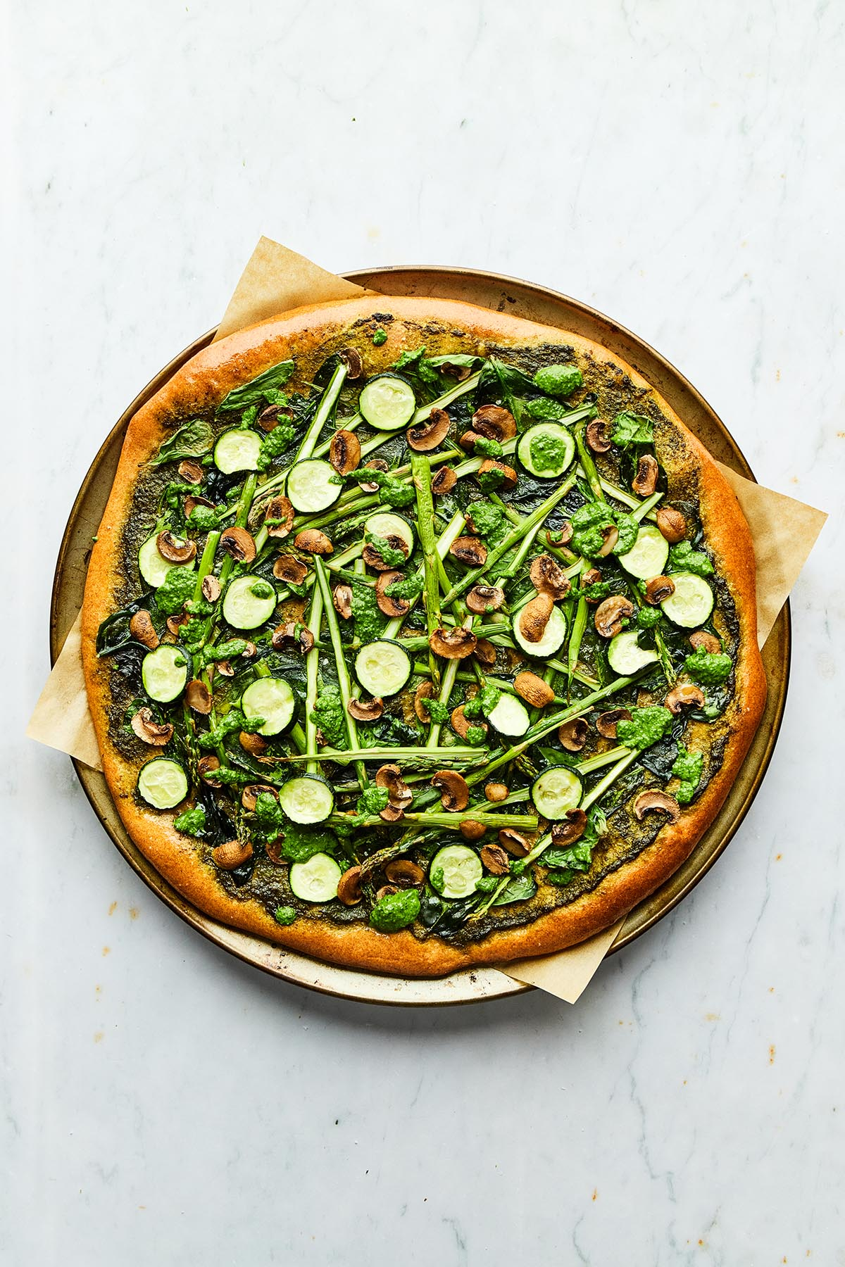 A fully baked spring pesto pizza on a round baking tray lined with parchment paper.