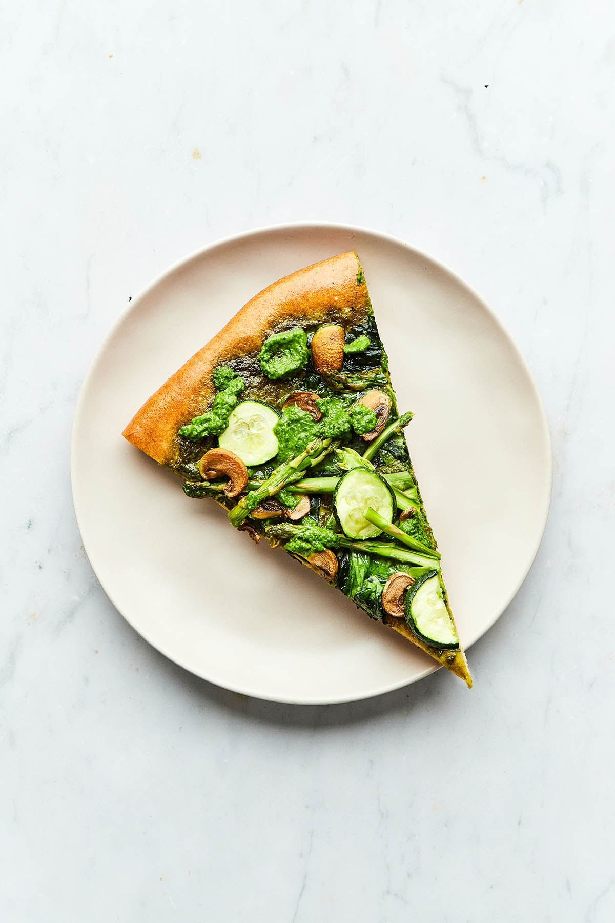 A slice of pesto pizza on a plate.