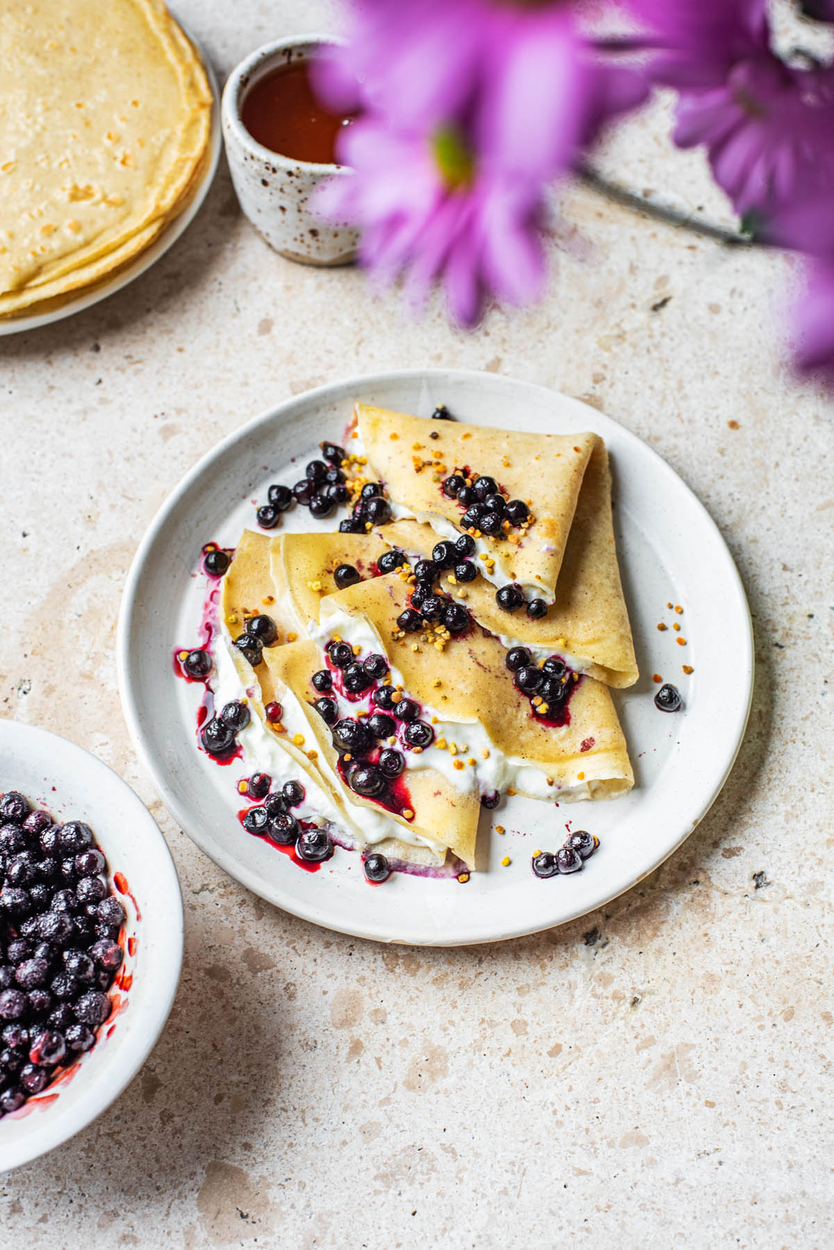 Folded crepes with extra berries and crepes nearby.