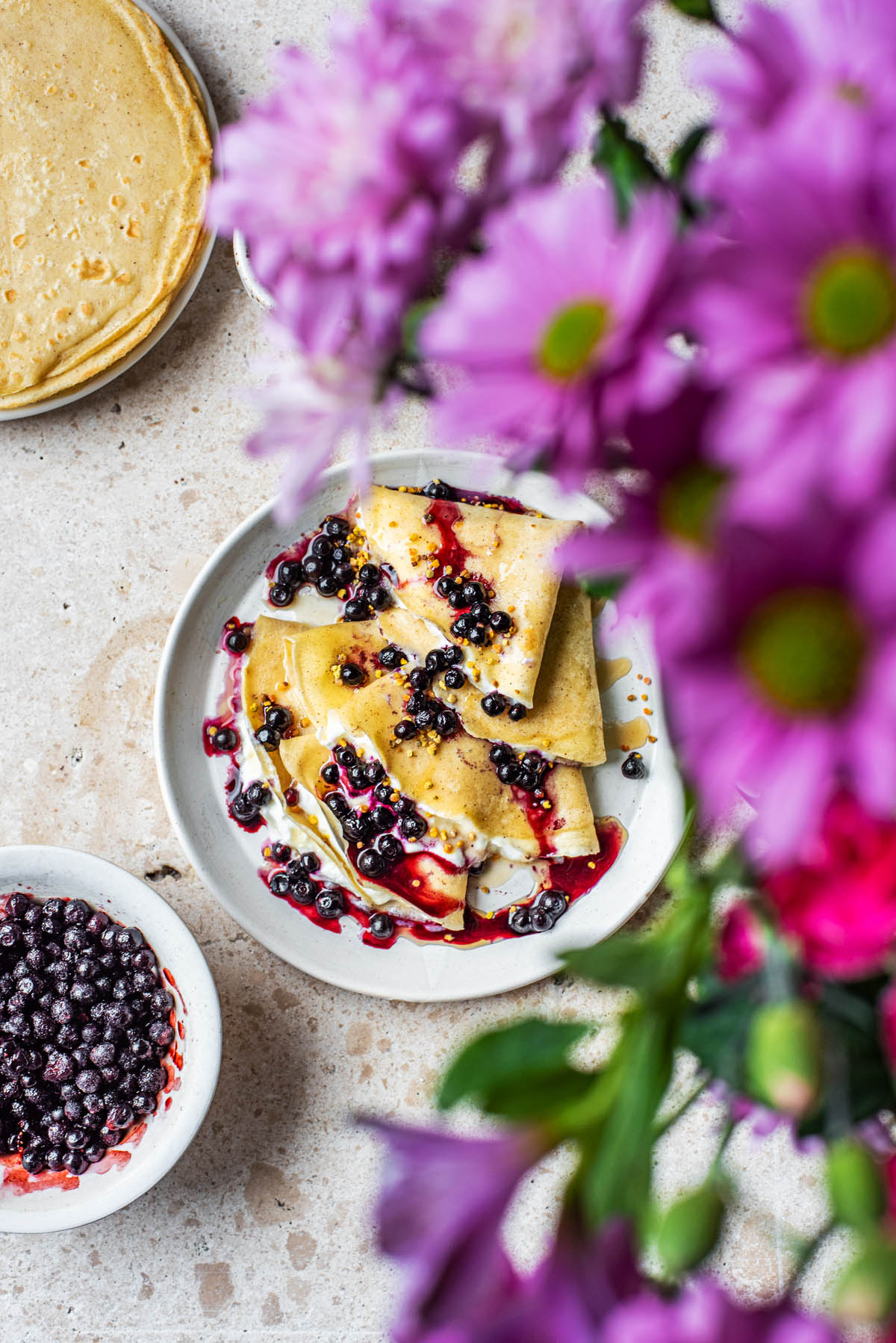 Overhead shot of crepes with flowers.
