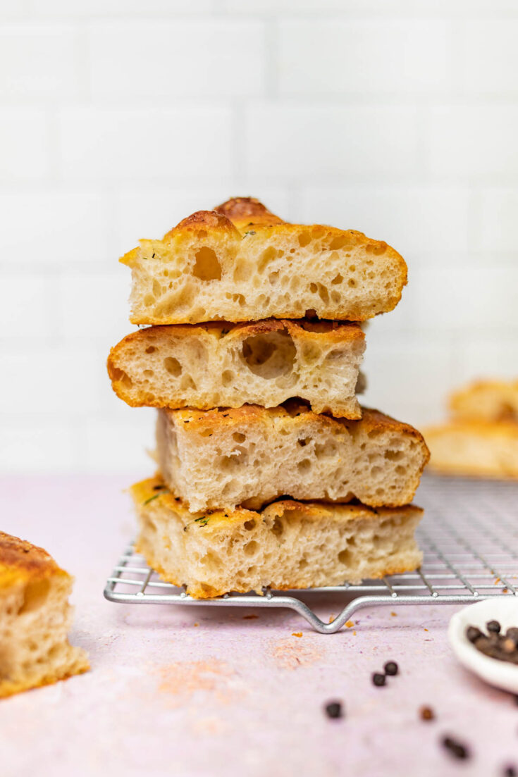 Four pieces of bread, stacked, on a cooling rack.