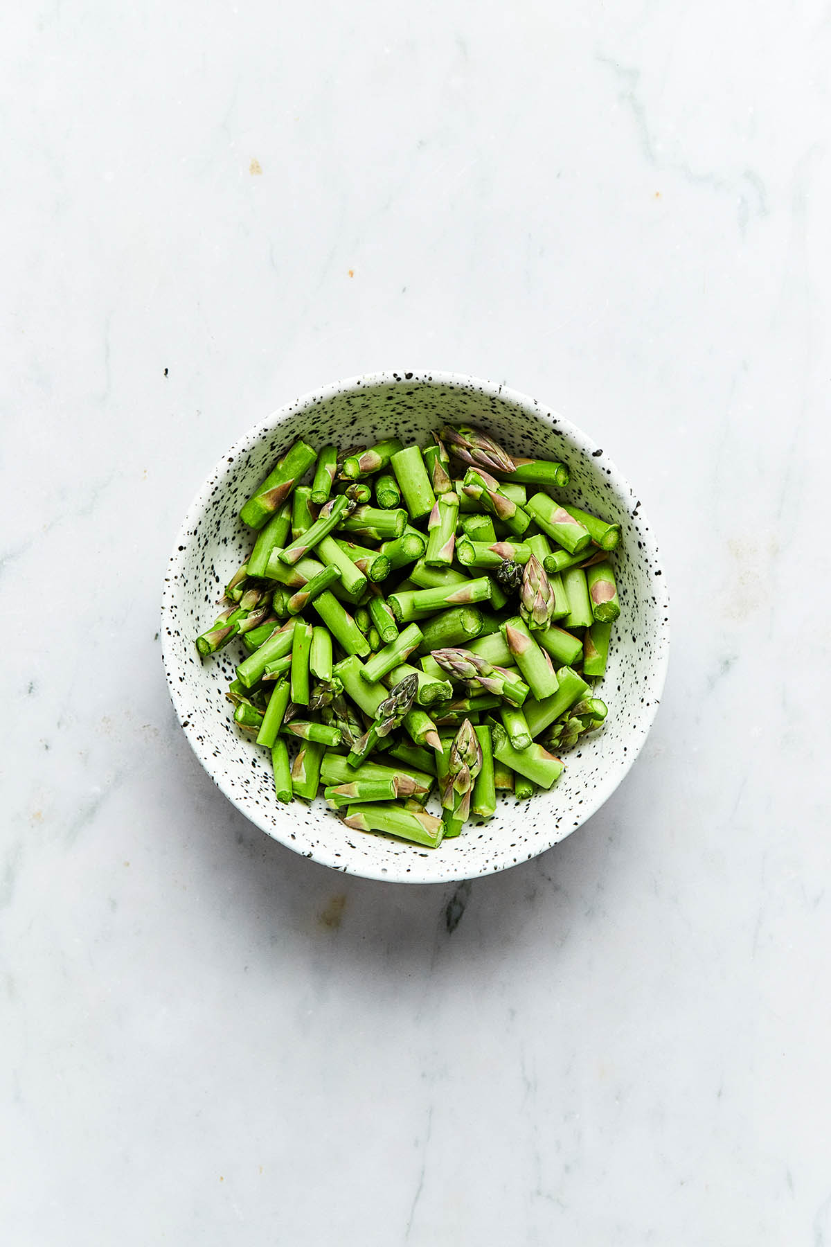A bowl of uncooked chopped asparagus.