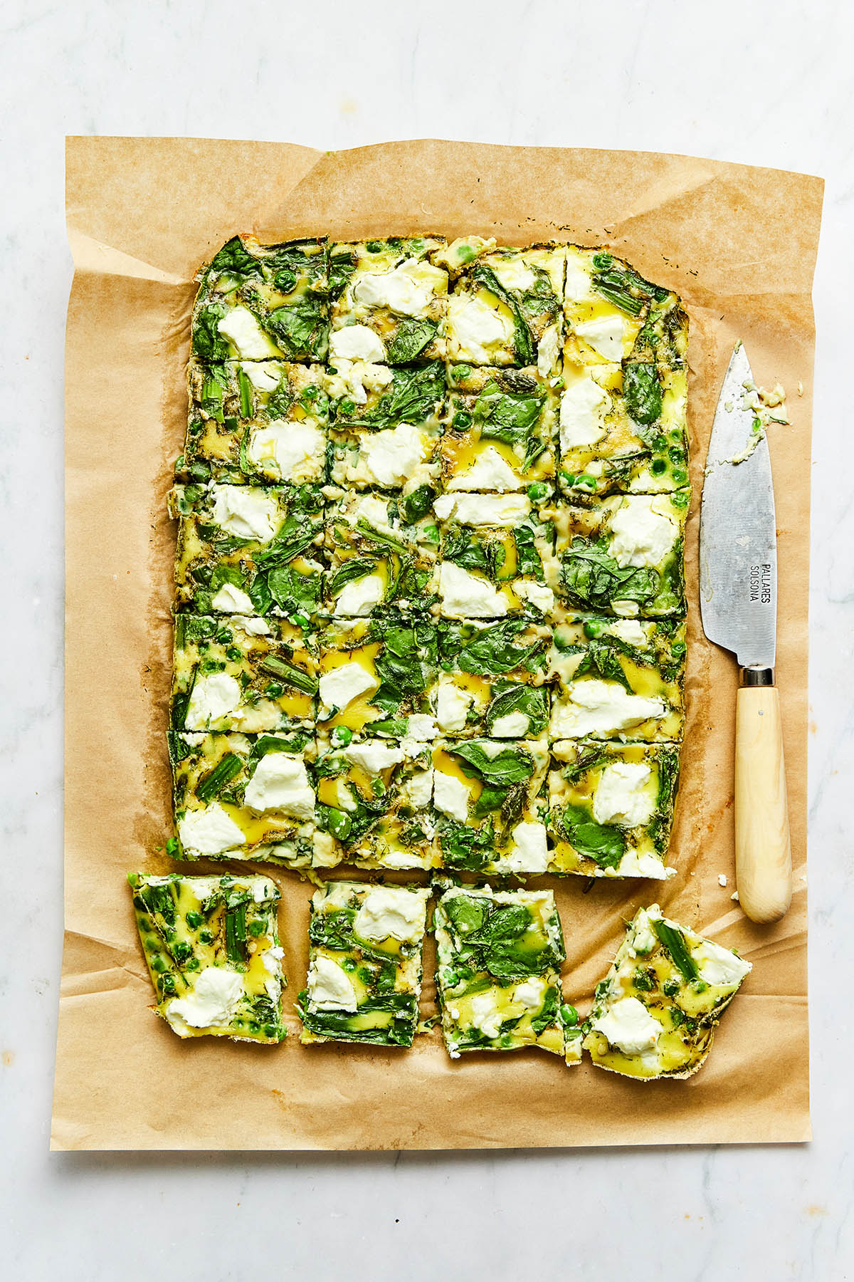 A sliced baked asparagus frittata on parchment paper with a knife alongside the paper.