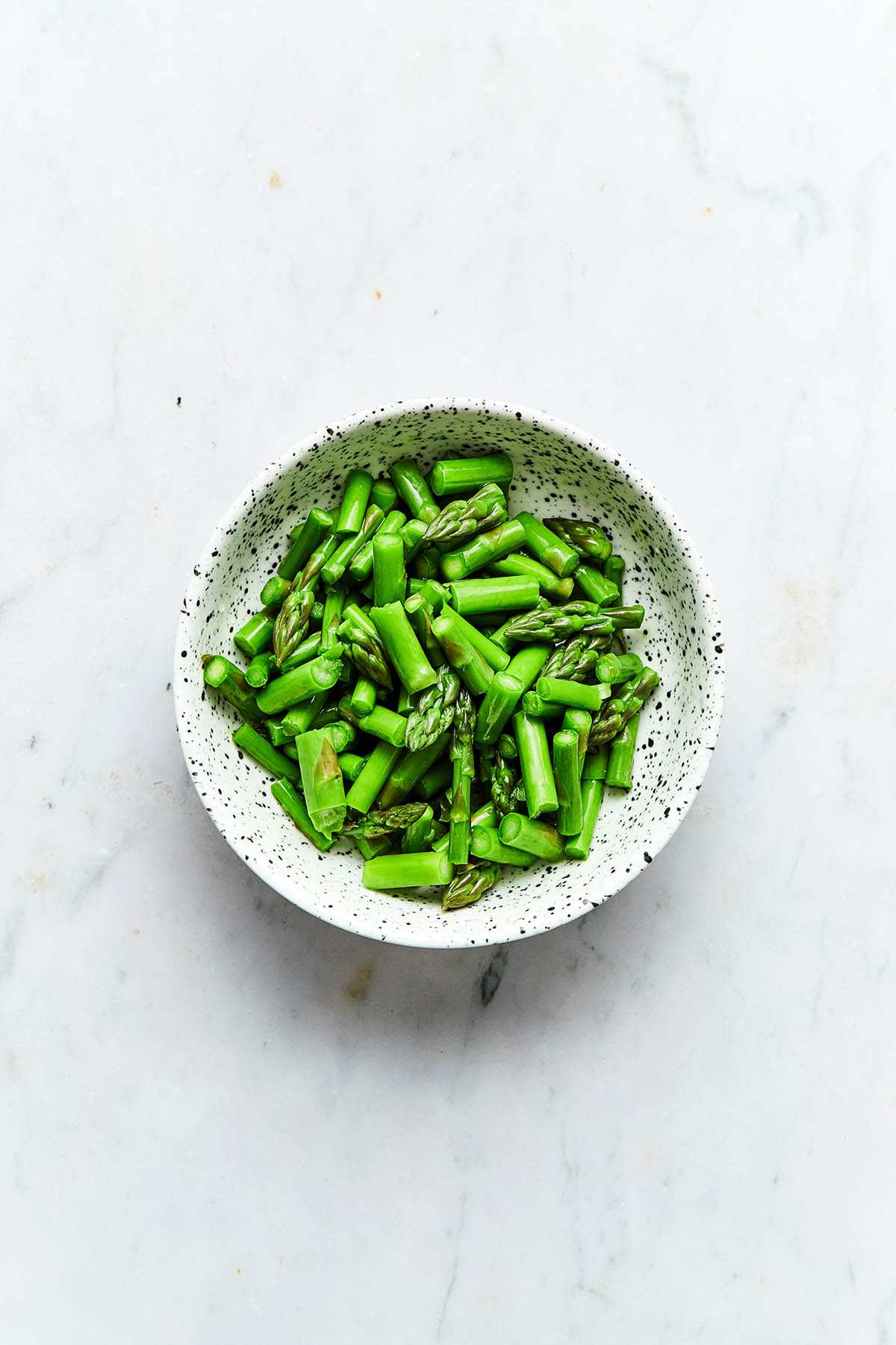 A bowl of blanched chopped asparagus.