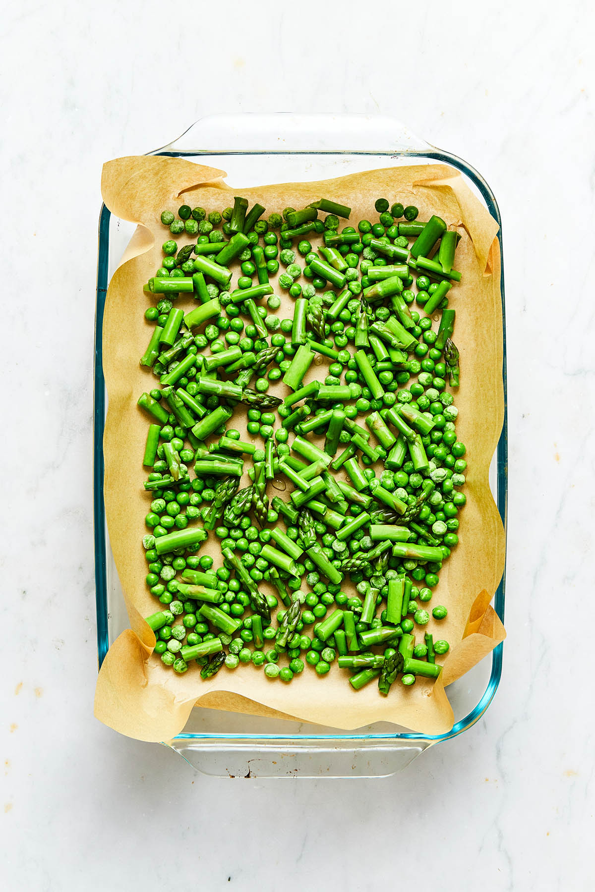 Blanched asparagus and green peas scattered inside a parchment paper-lined baking dish.