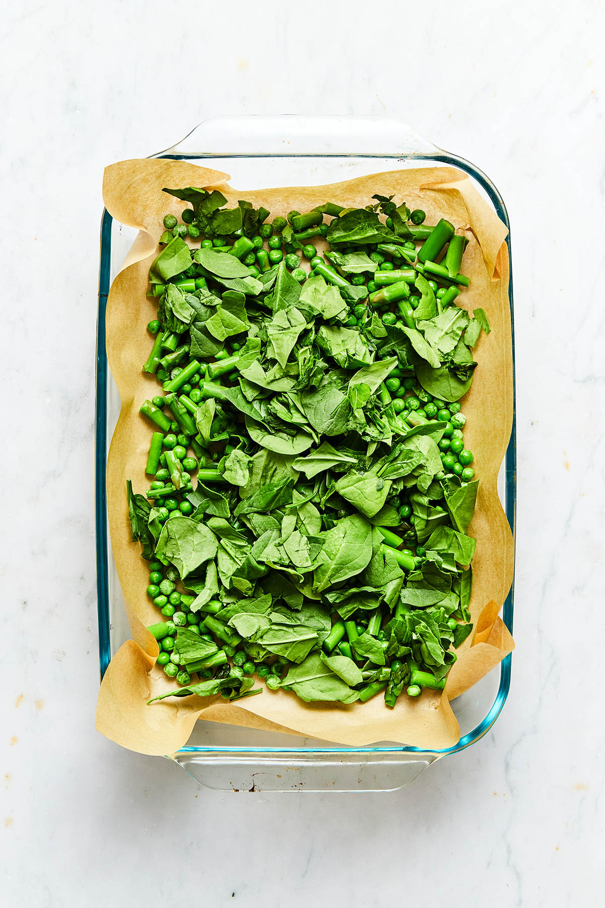 Torn baby spinach leaves, chopped blanched asparagus, and green peas inside a baking dish lined with parchment paper.