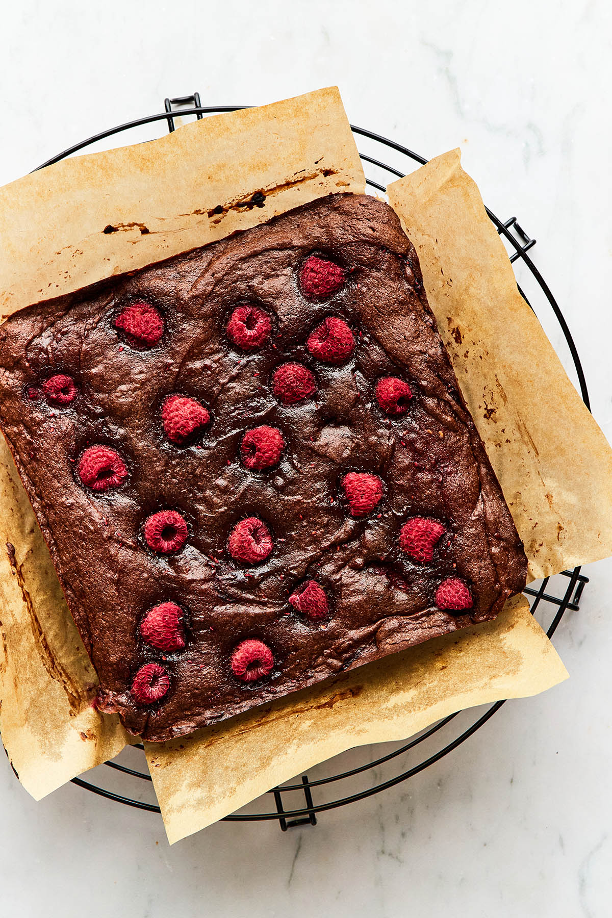 uncut raspberry brownies still on parchment paper on a cooling rack.