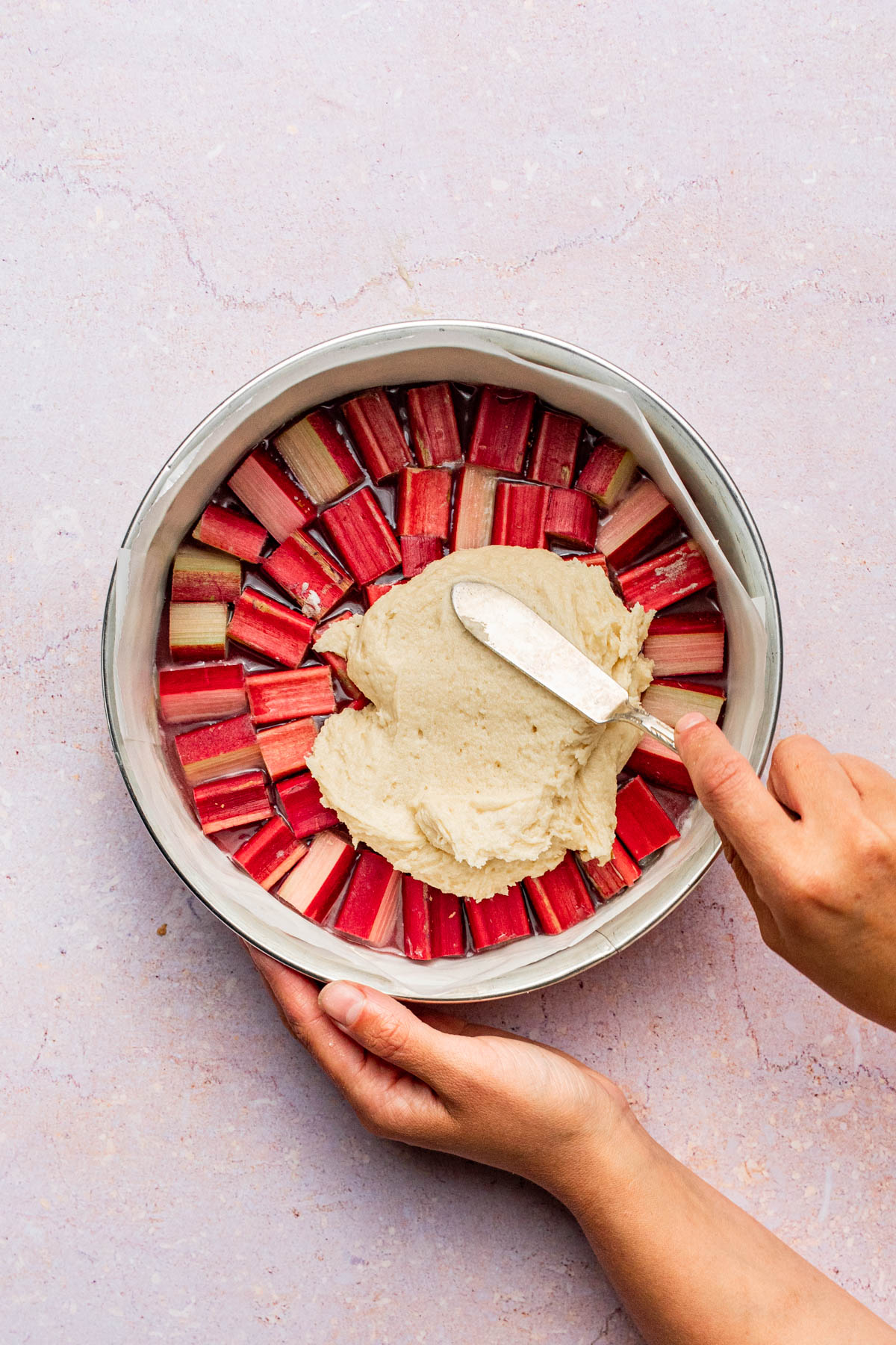 Cake batter being spread over rhubarb.