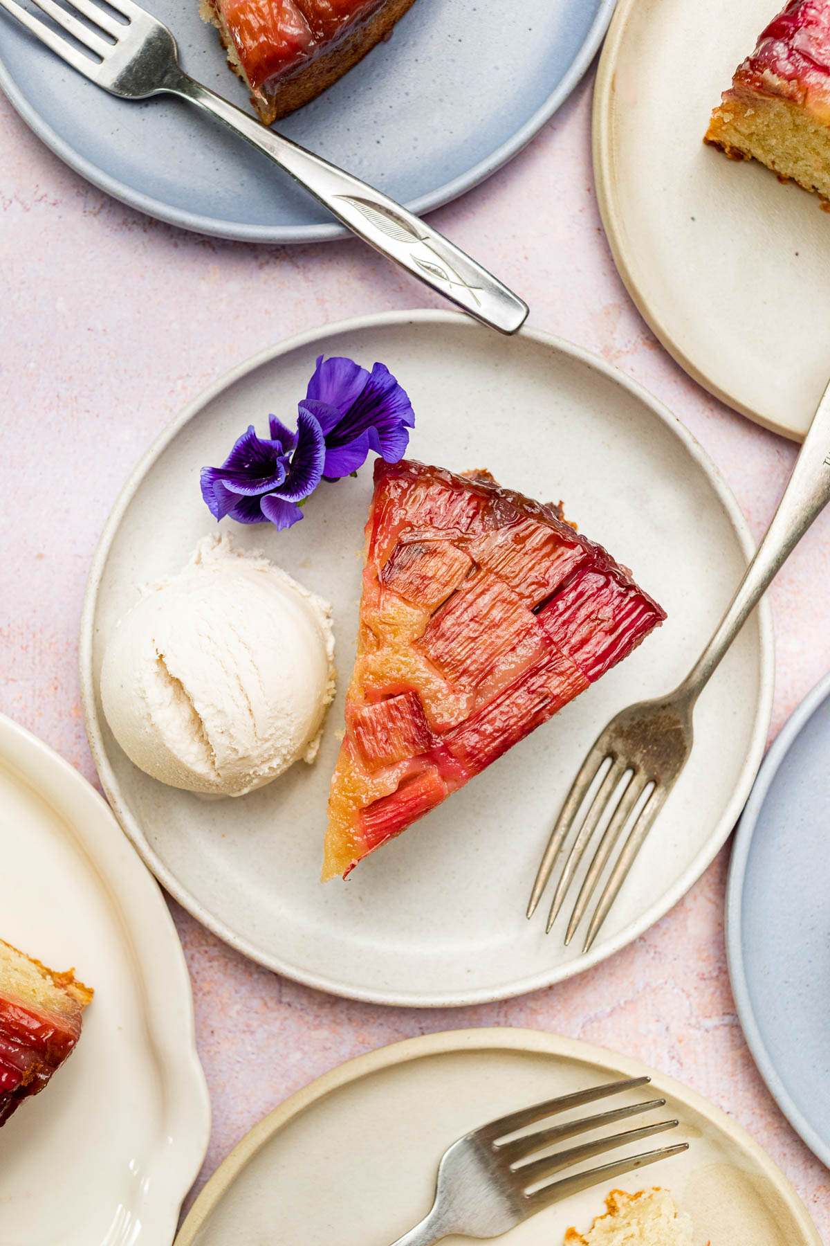 Slices of cake on plates with ice cream and flowers.