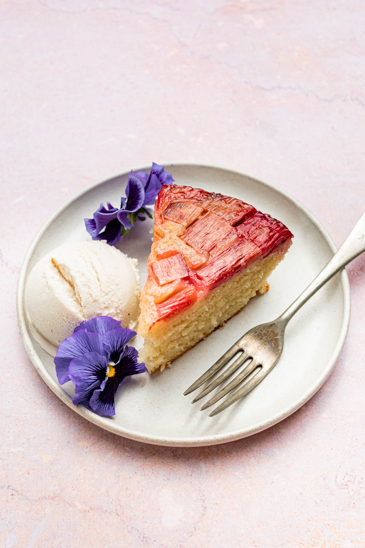 A slice of cake with ice cream and flowers.