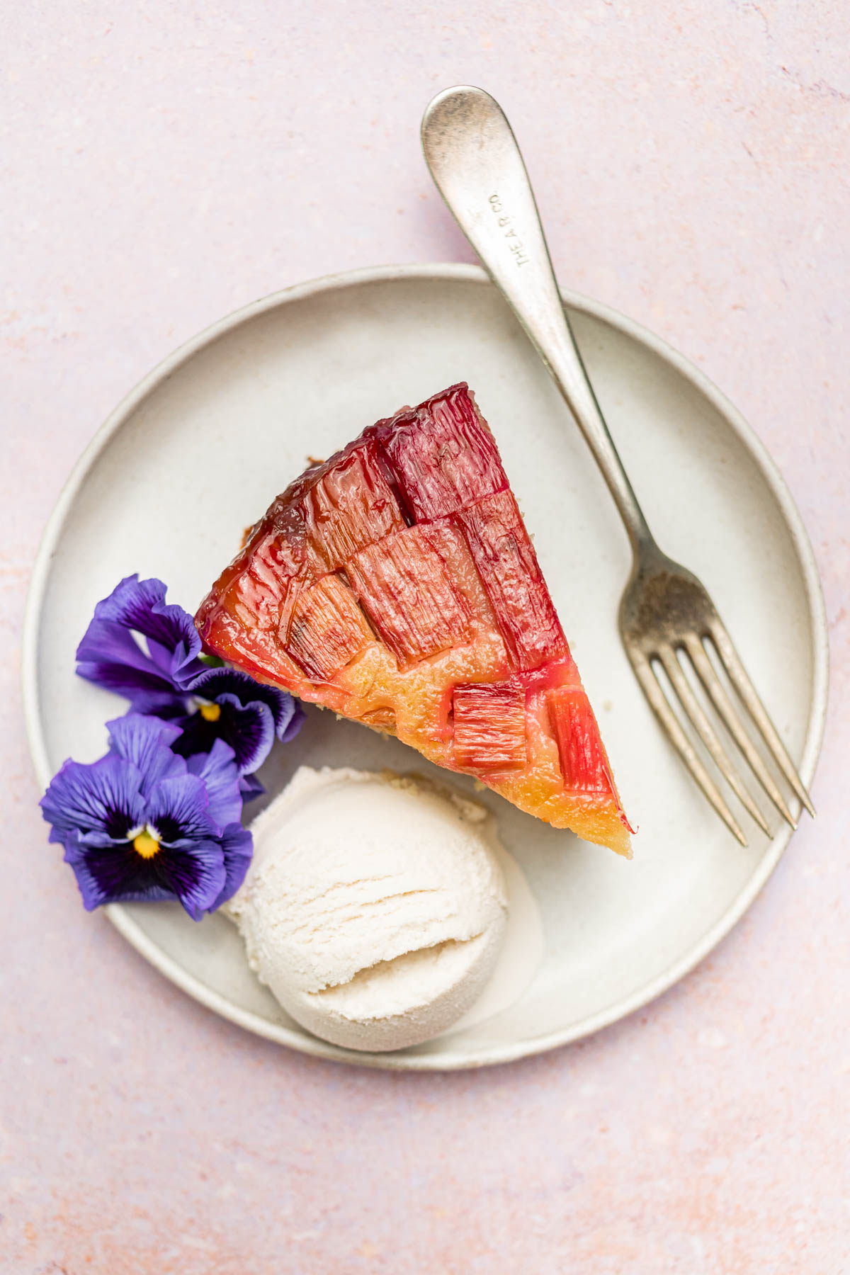 Slice of rhubarb cake with ice cream and pansies.