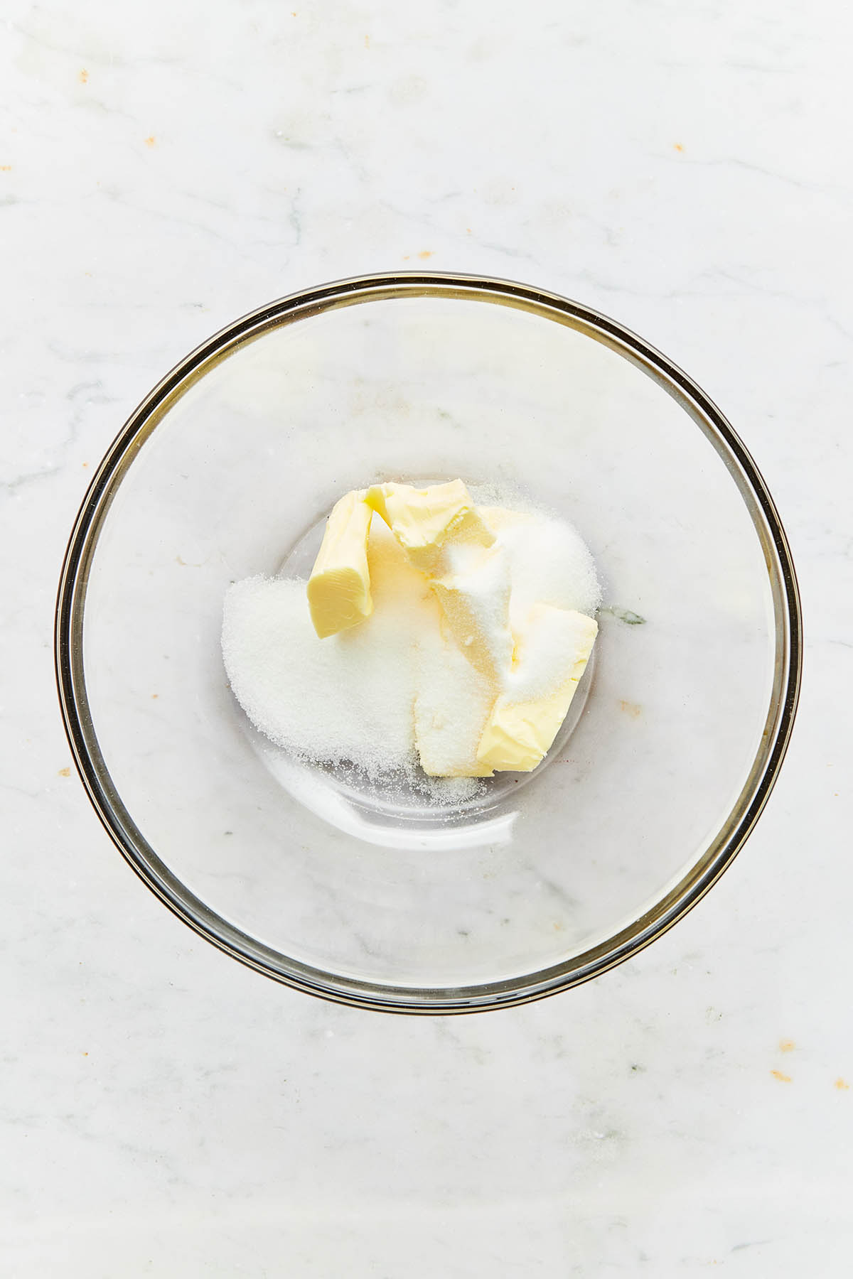 Sugar and butter in a mixing bowl.