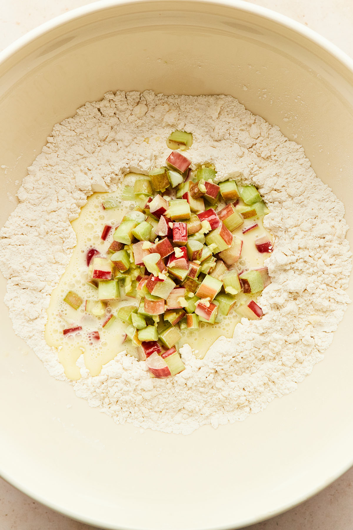 A bowl of flour with an egg-cream-rhubarb mixture in the middle to be folded in.