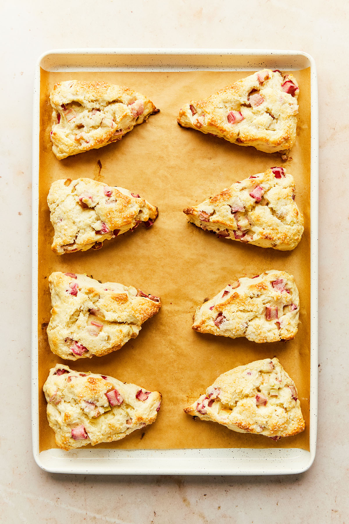 A baking sheet lined with parchment paper topped with eight baked rhubarb scones.