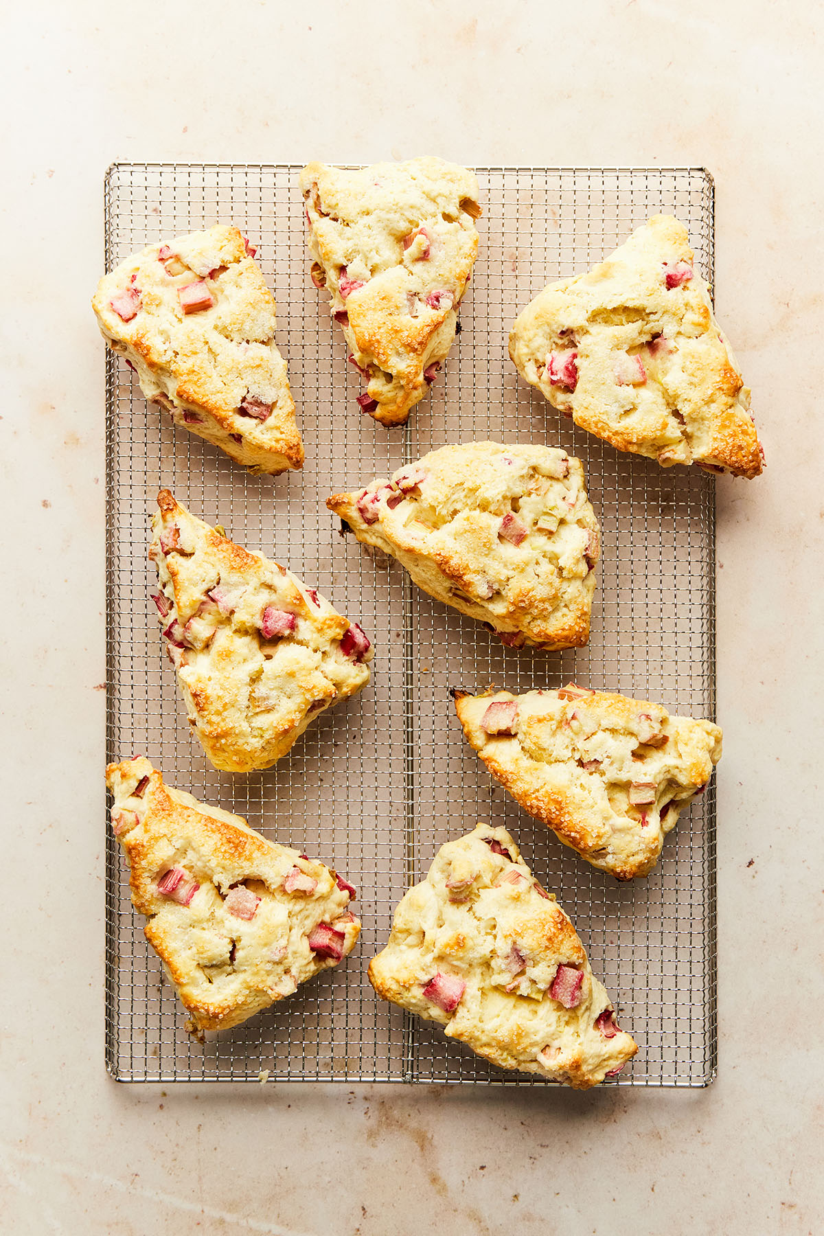 A cooling rack with eight rhubarb scones on it.