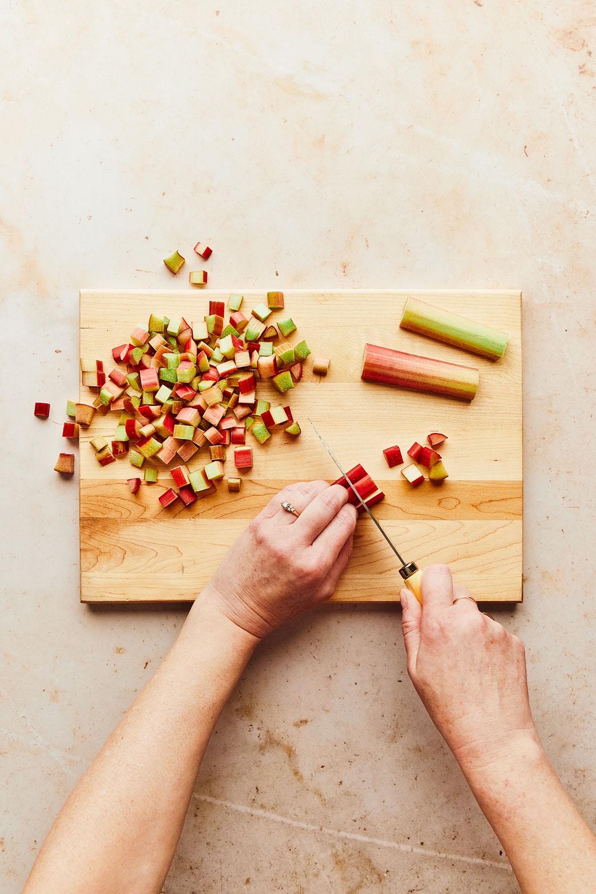 Hands chopping fresh rhubarb on a wooden cutting board.