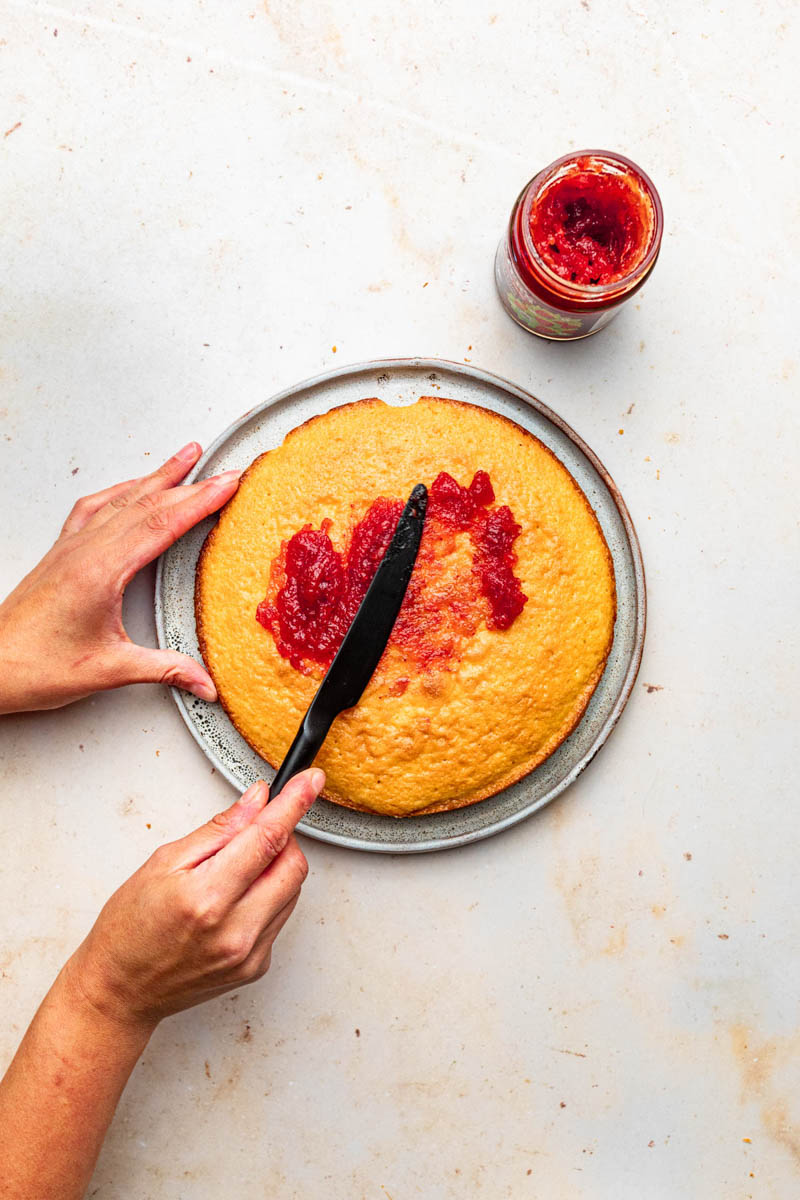 Strawberry jam being spread on the top of a cake.