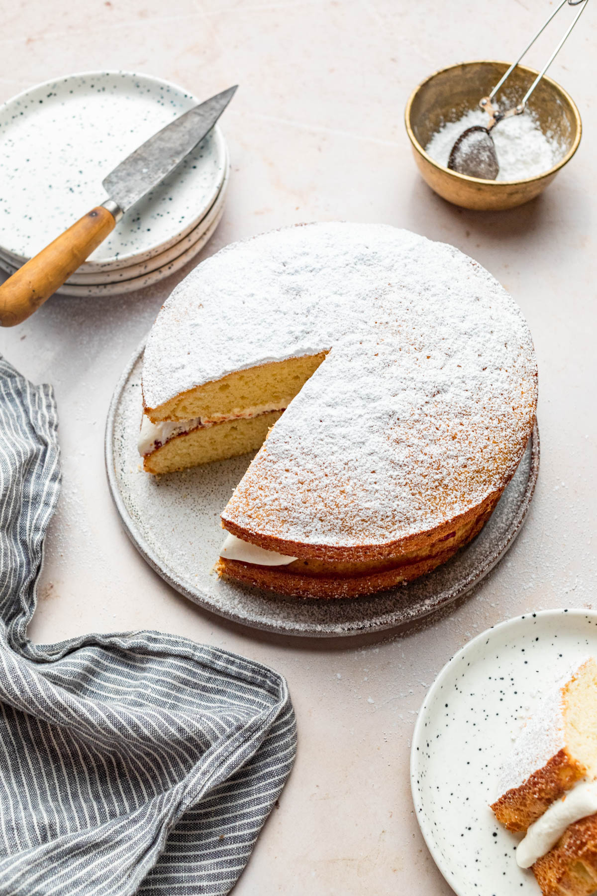 Icing sugar topped layer cake with one slice out.
