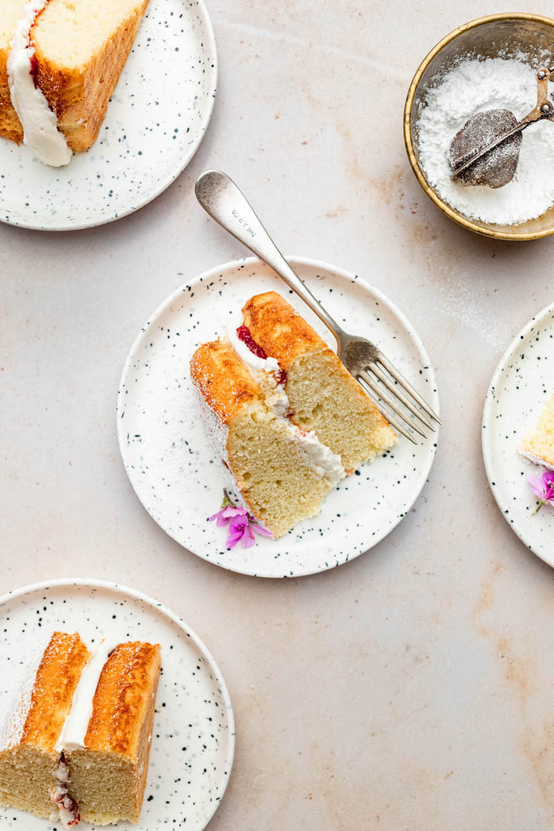 Slices of layer cake on small plates with forks.
