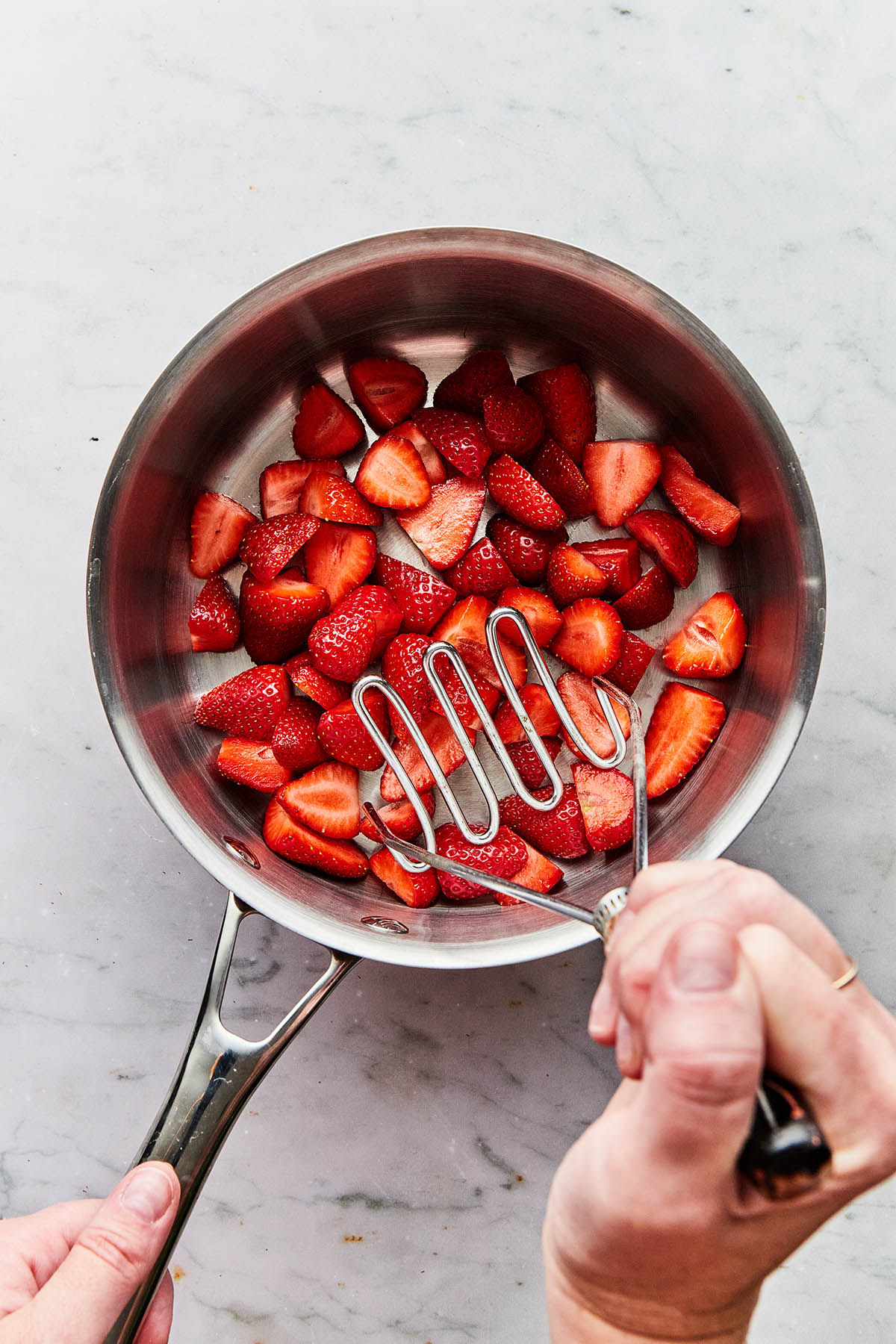 A hand holding a potato masher about to crush strawberries in a pot.