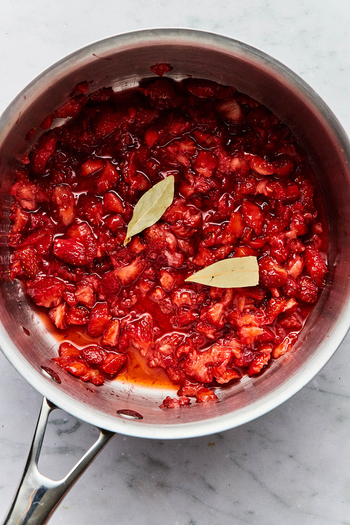 Mashed strawberries and two bay leaves in a pot.