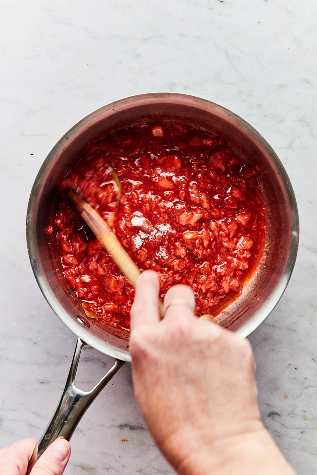 A hand using a wooden spoon to quickly stir sugar and pectin into a pot of cooked strawberries.