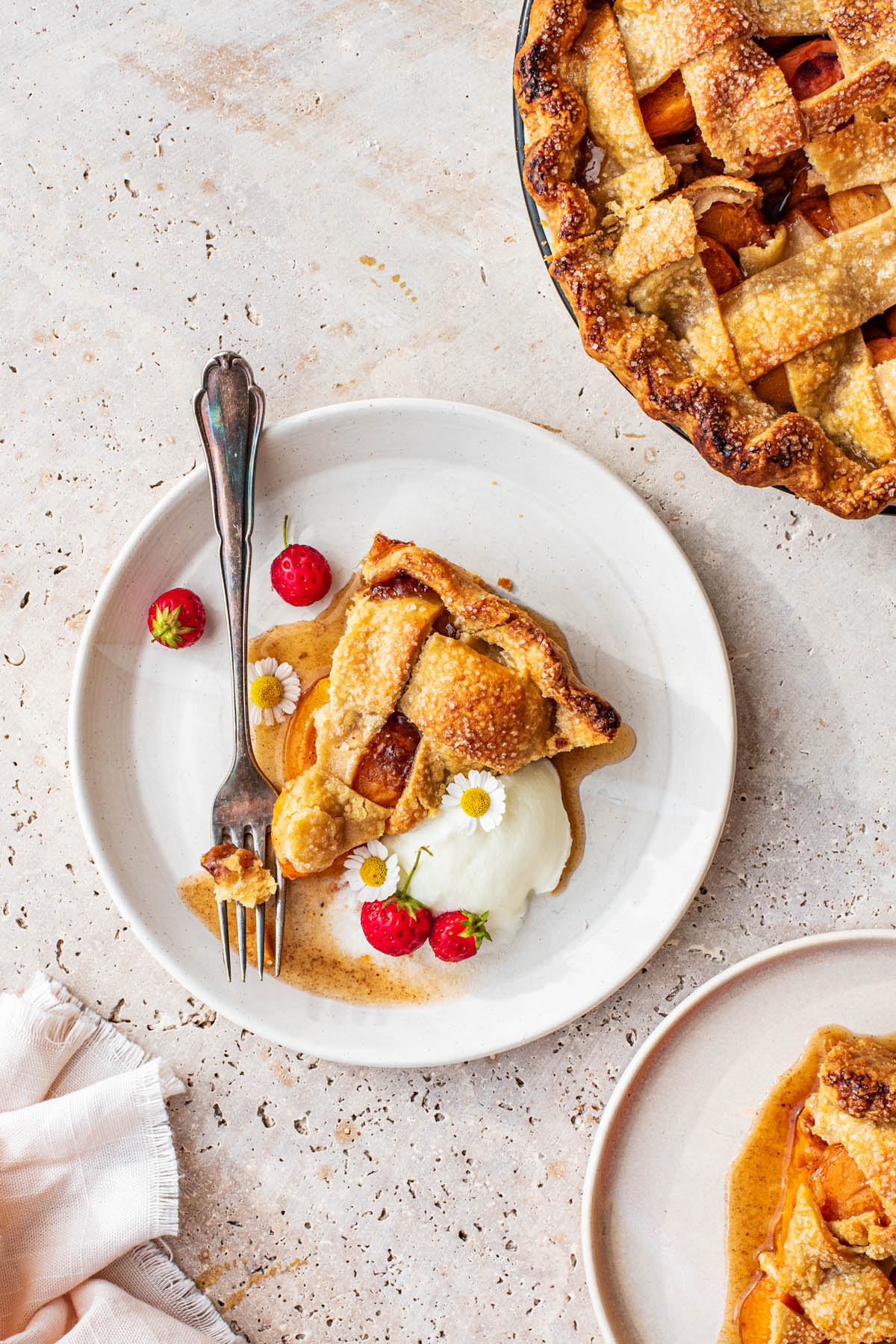 Pie slices on plates, with yogurt, fresh berries, and edible flowers.