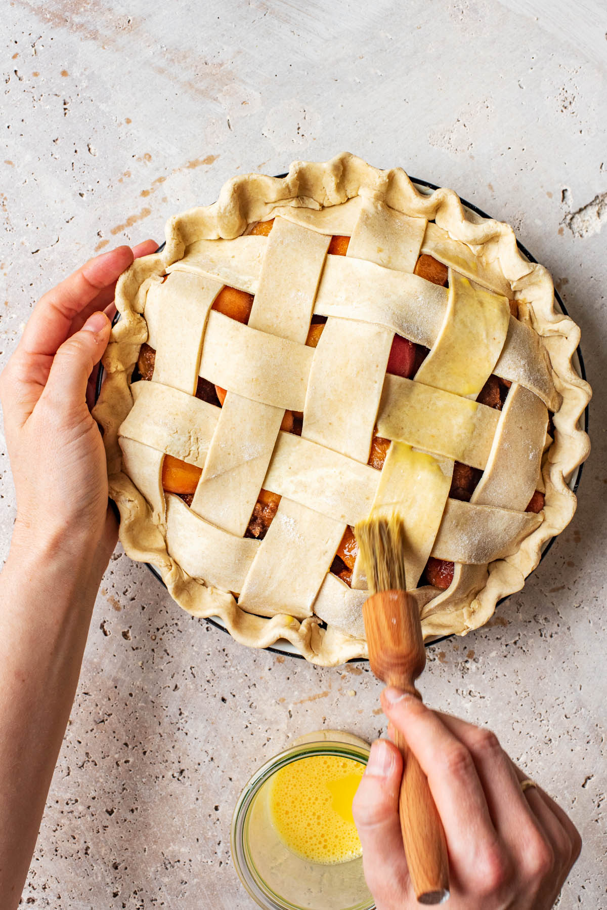 Woman's hands brushing egg wash onto lattice pie with a small wooden brush.