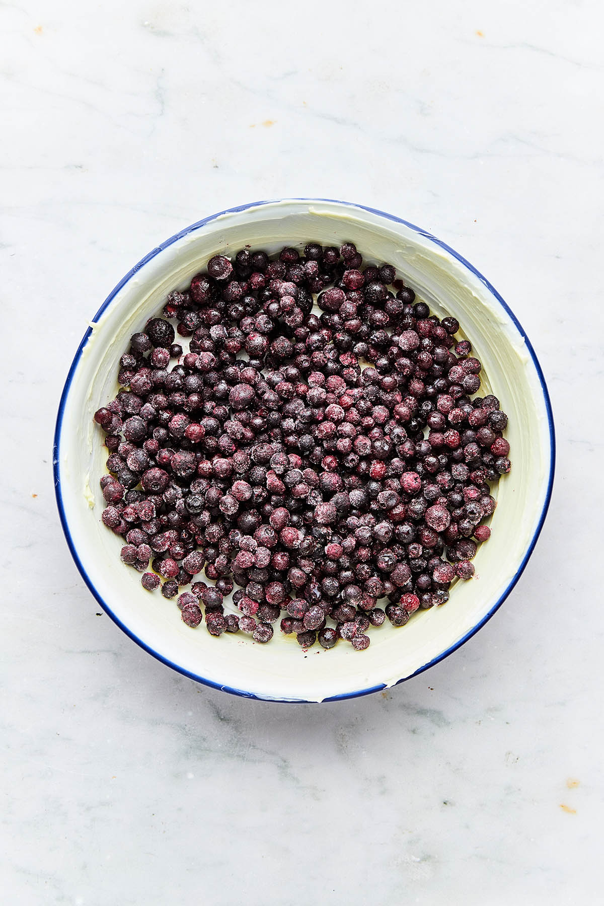 Frozen blueberries in a buttered baking dish.