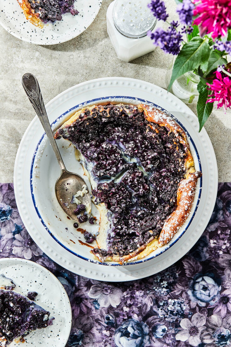 A baking dish of blueberry clafoutis with some spooned out onto plates.