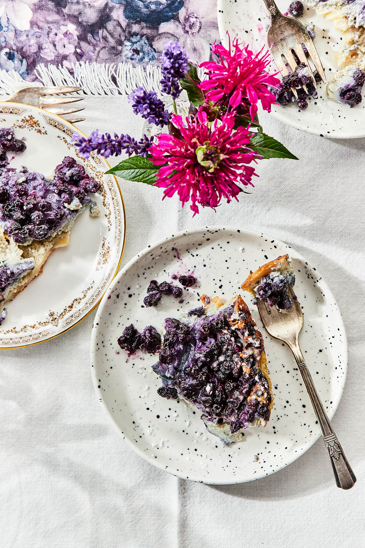 servings of blueberry clafoutis on dessert plates on a white tablecloth with a small vase of flowers.