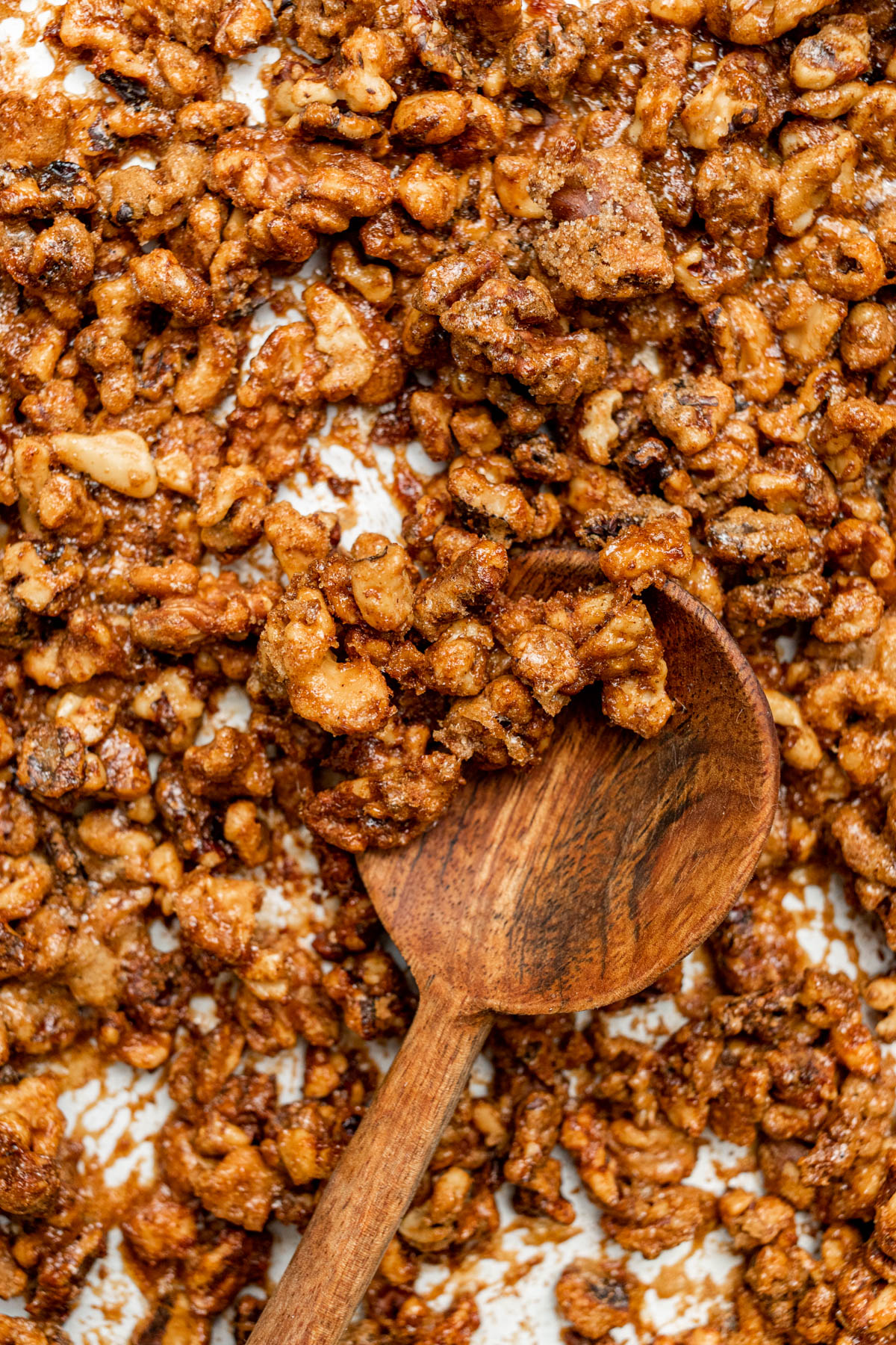 Candied walnuts on a baking sheet along with a decorative wooden spoon.