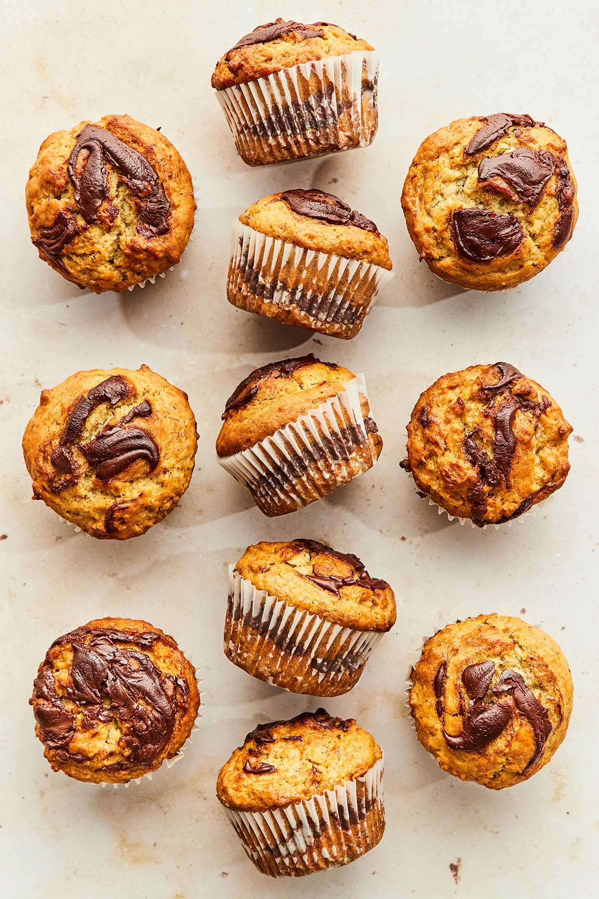 Banana Nutella muffins on a warm-coloured marble surface.