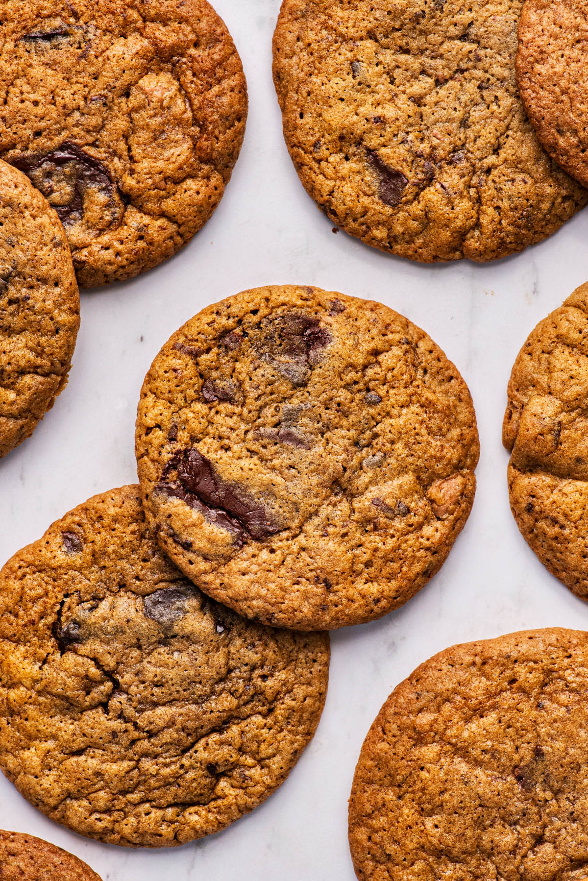 Several chocolate chunk cookies on a pale marble background.