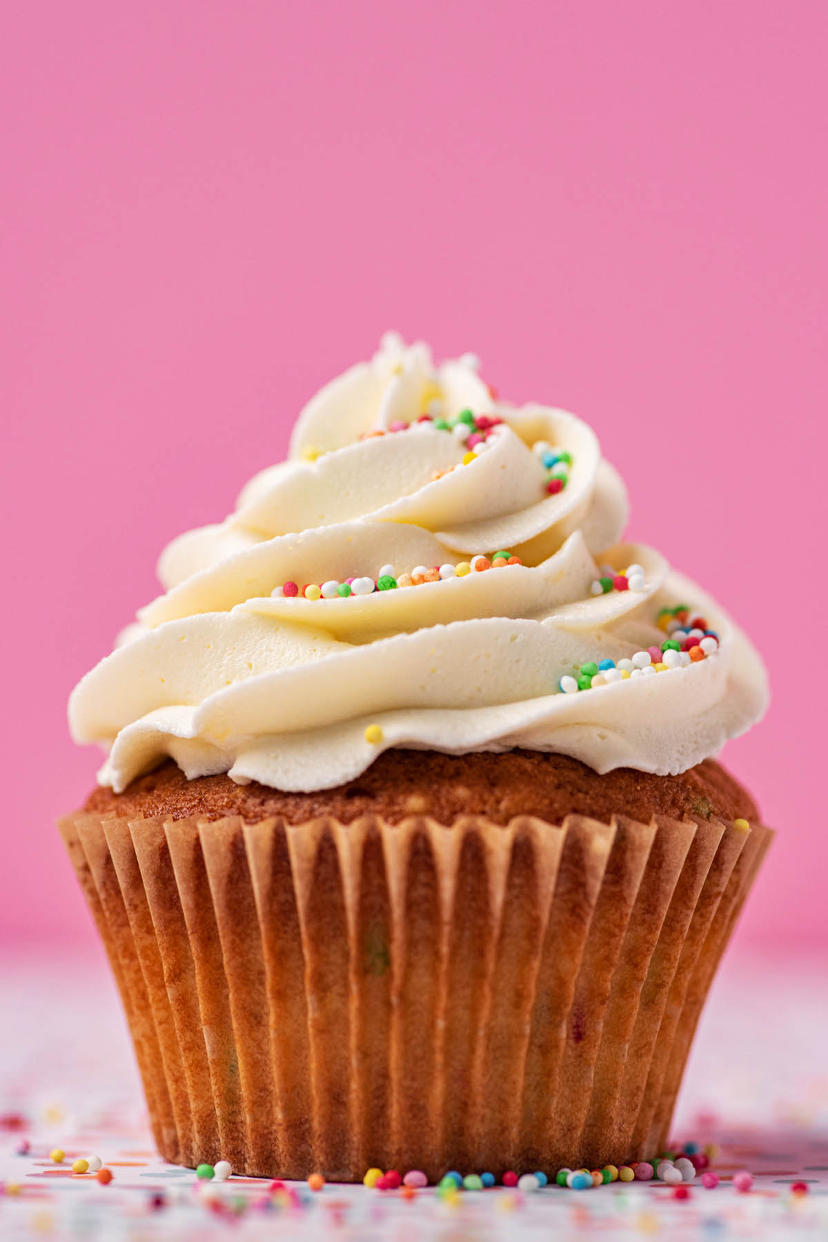 Close up of a buttercream frosted cupcake with small rainbow sprinkles.