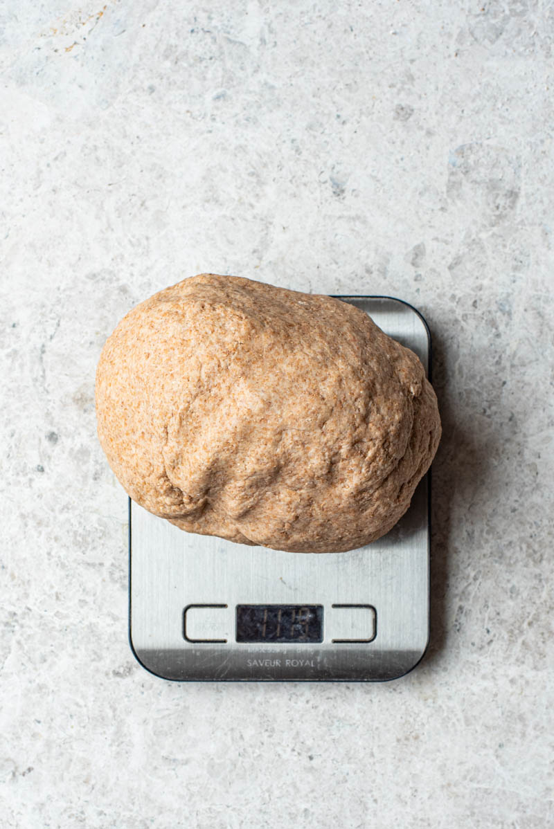 Weighing the rested dough to determine how big the bagels should be.
