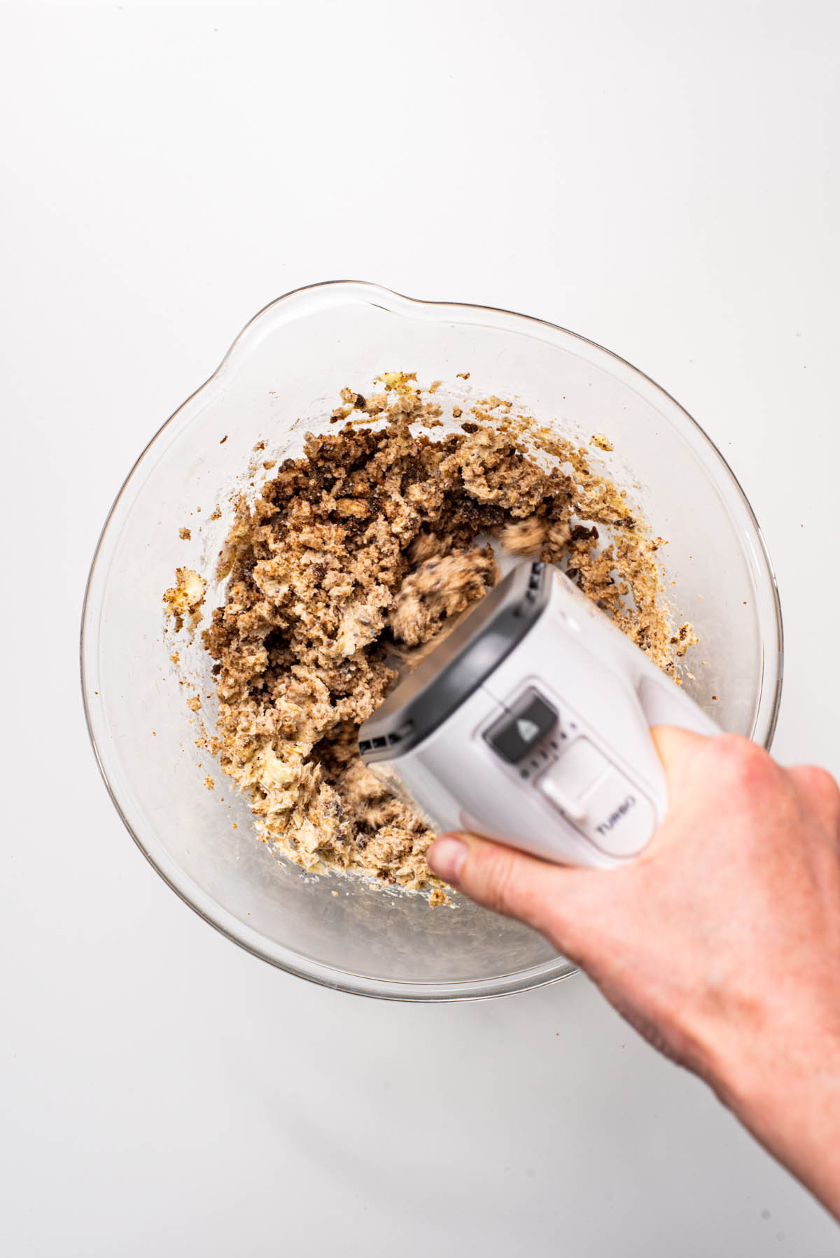 Mixing sugars and butter with an electric hand mixer.